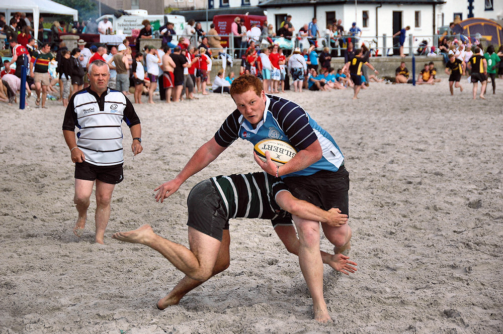 Picture of a player being tackled during a beach rugby game