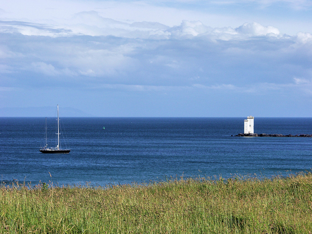 Picture of a sailing yacht anchored in a bay with a lighthouse at the end of the bay
