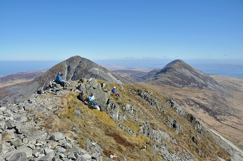 Picture of walkers on the summit of a mountain, two other mountains in the background