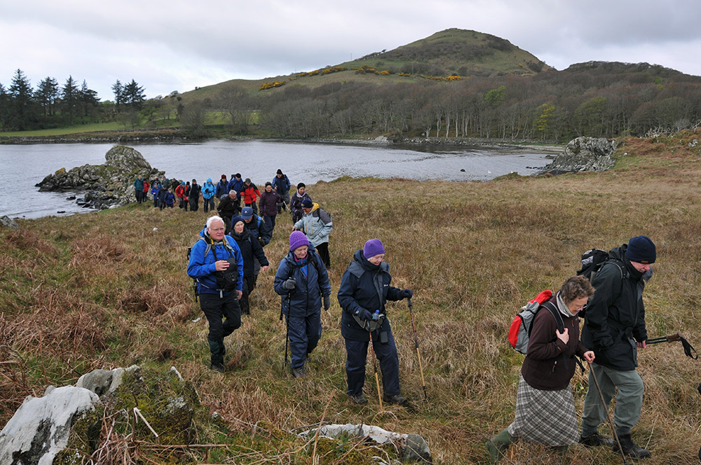 Picture of a group of walkers near a bay, also a hill in the background