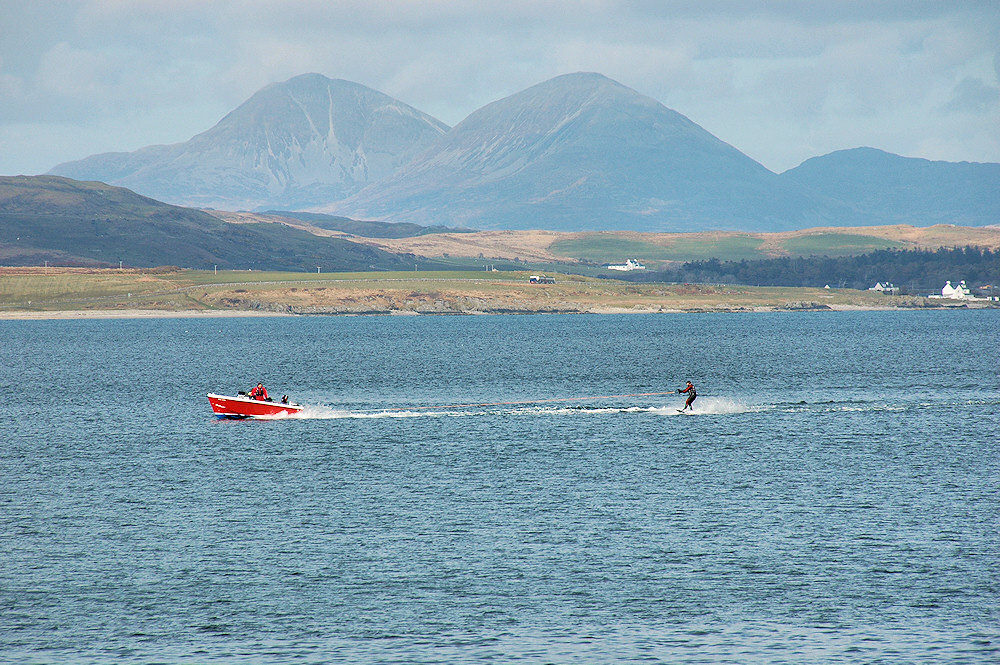 Picture of a boat pulling a waterskier on a sea loch, mountains in the background