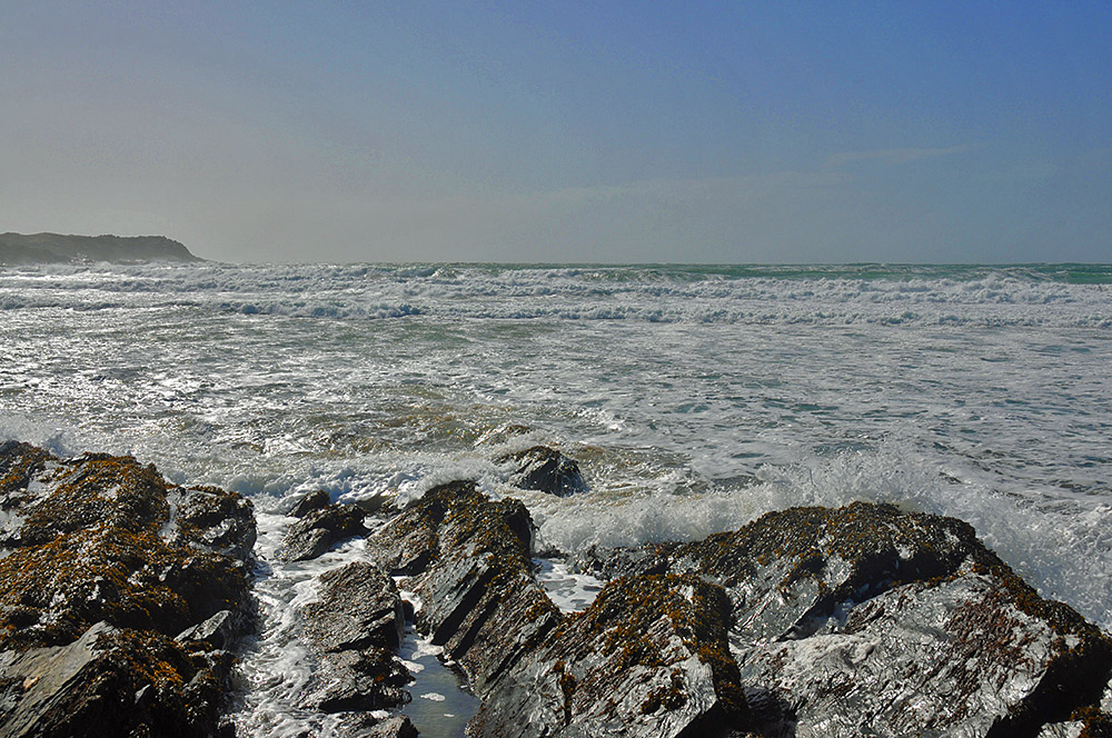 Picture of waves rolling into a bay with rocky outcrops on a beach