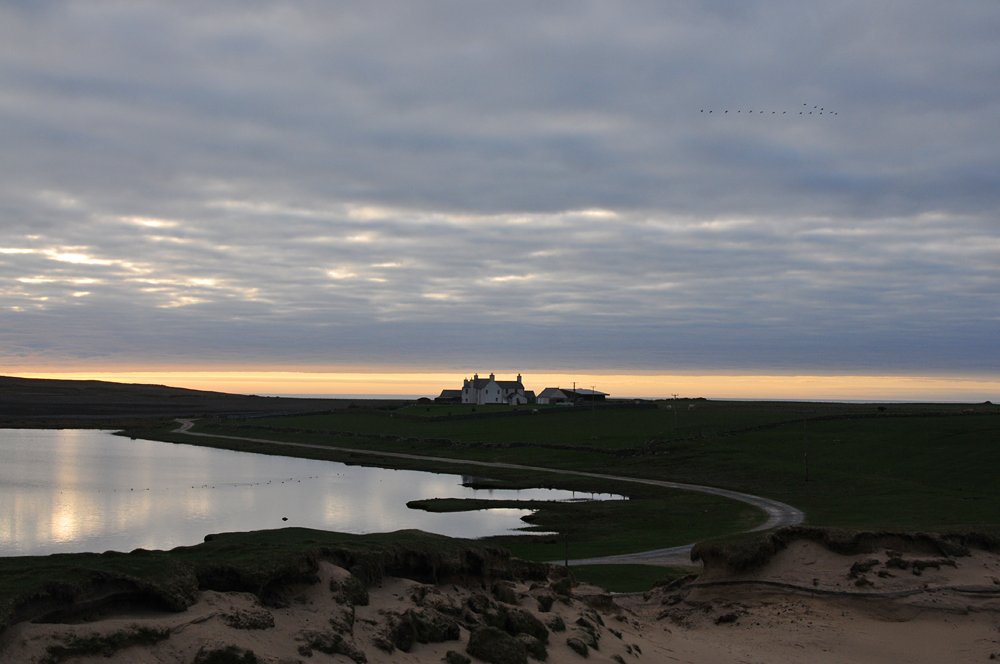 Picture of a farm building next to a small loch in the evening light, clouds moving in