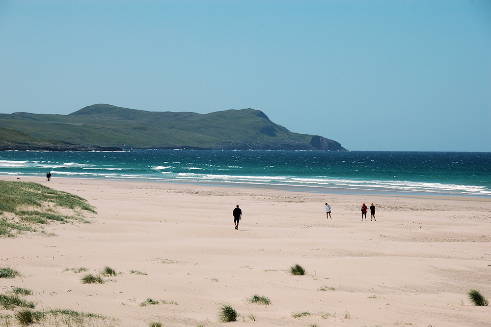 Picture of a wide sandy beach with a few people walking on it