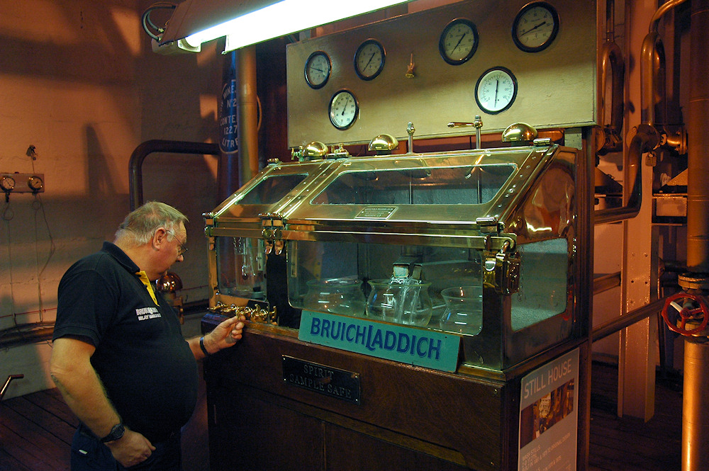 Picture of a man adjusting the flow at a whisky distillery spirit safe
