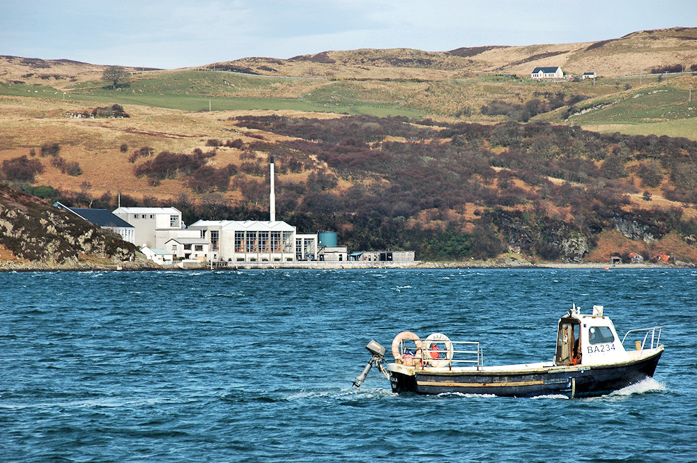 Picture of a fishing boat passing a coastal distillery