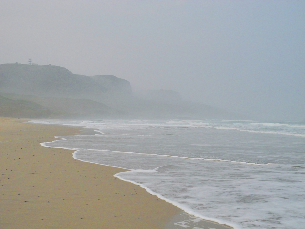 Picture of a beach in a bay with fog rolling in