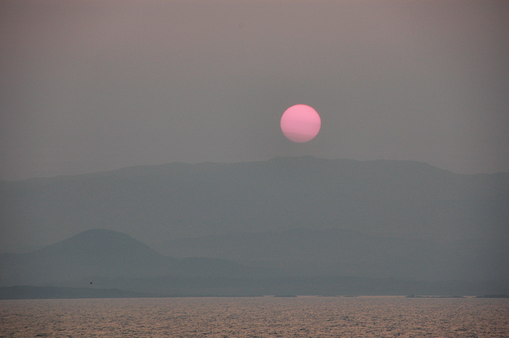 Picture of a hazy sunset with a red sun over island, seen from a ferry