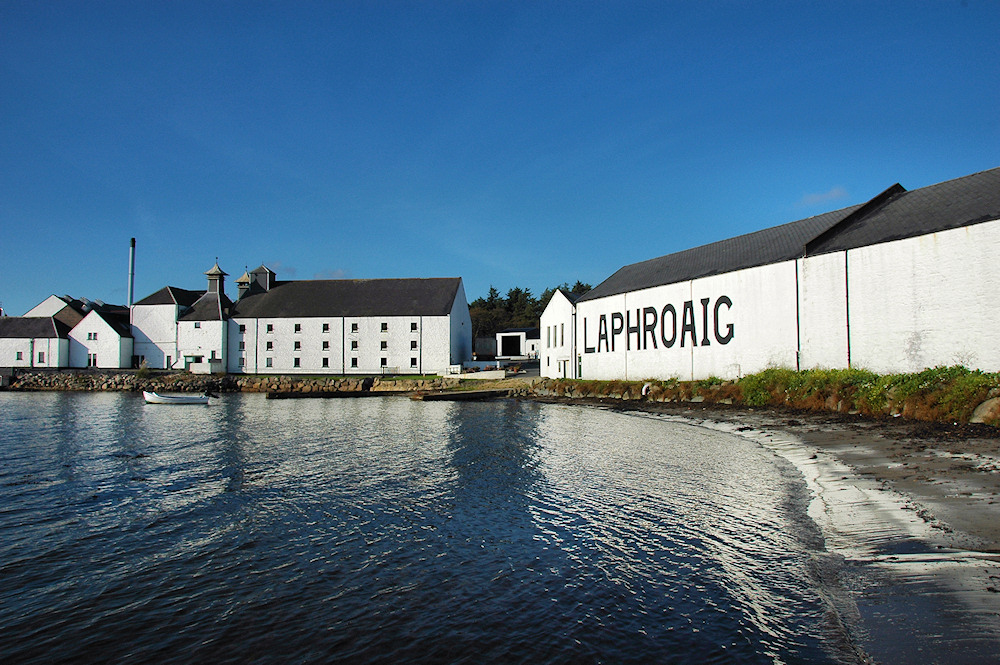 Picture of Laphroaig distillery from the shore on a bright sunny day