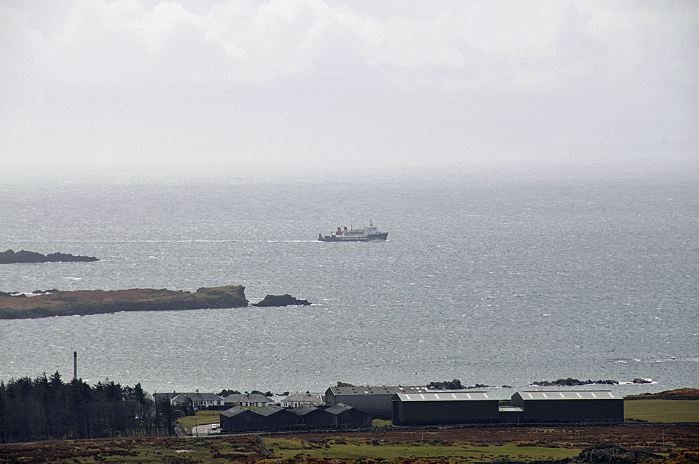 Picture of large distillery warehouses on a shore with a passing Calmac ferry off shore