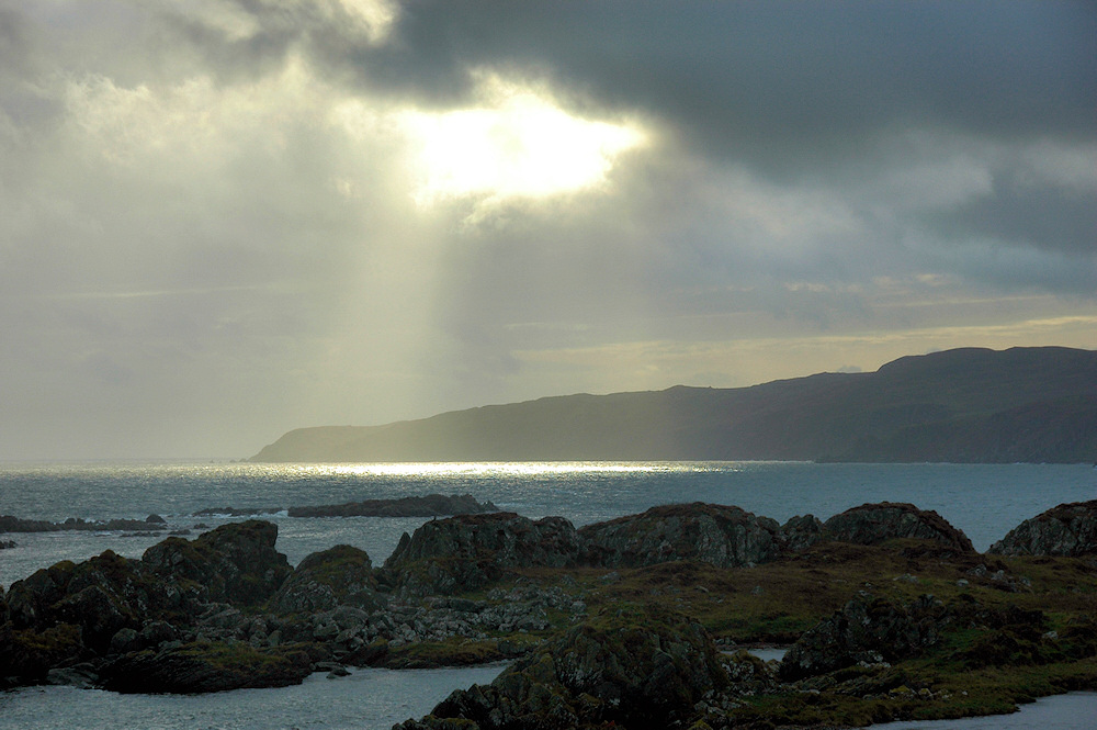 Picture of the sun breaking through clouds over a peninsula, illuminating the water below