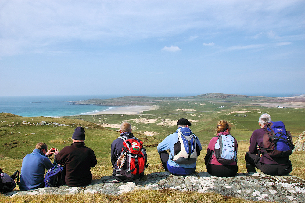 Picture of walkers sitting on a rocky ground high above a bay with a beach