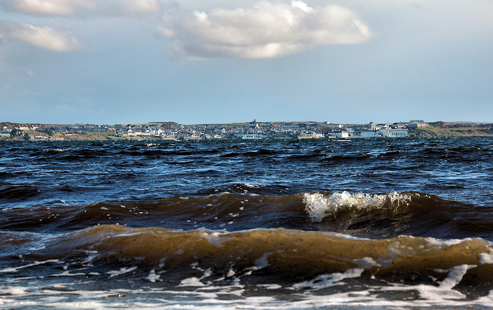 Picture of some small waves on a loch below a coastal village