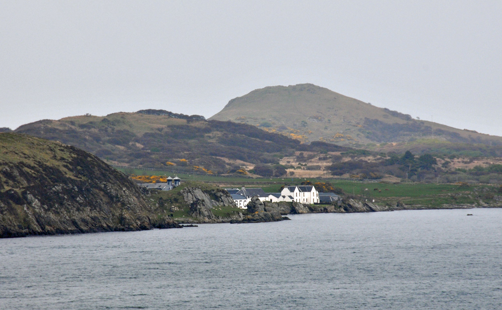 Picture of a partially visible coastal distillery, seen from an offshore small island