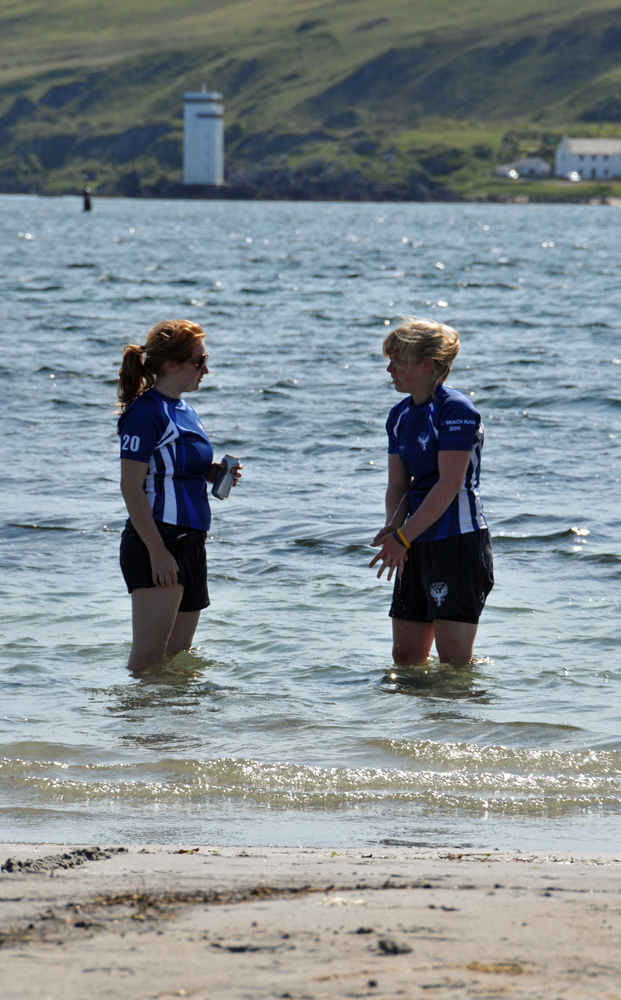 Picture of two female beach rugby players standing in the water, a lighthouse in the background