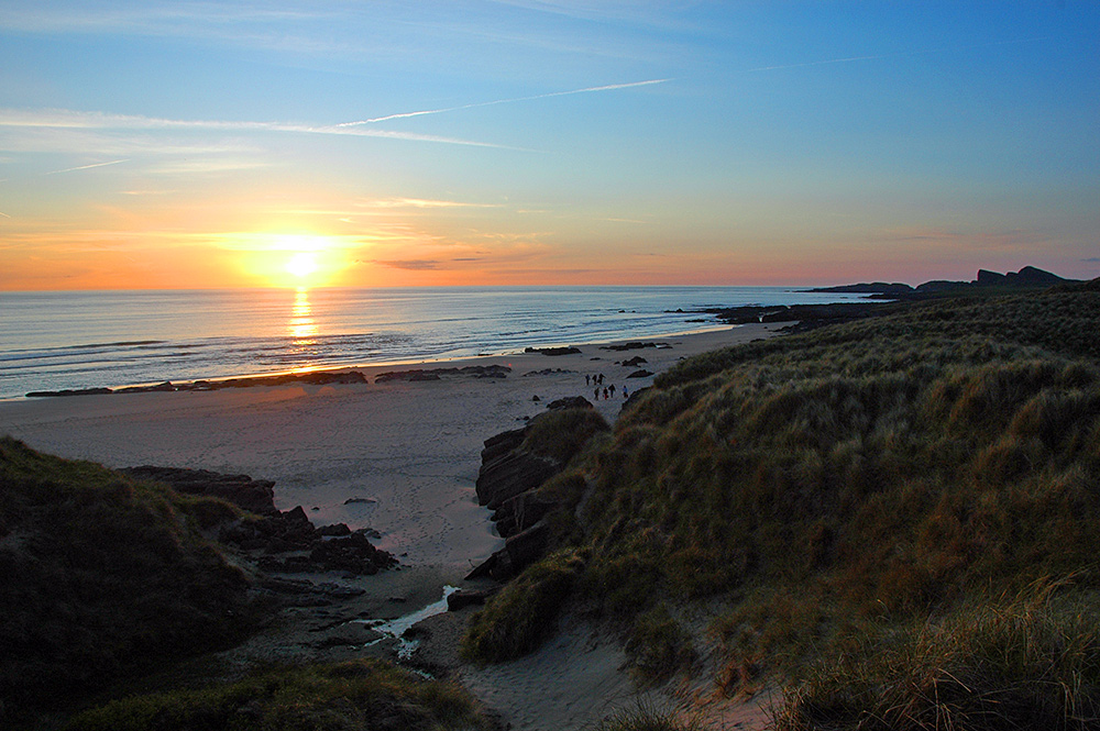 Picture of a sunset over a bay with a sandy beach, taken from the dunes