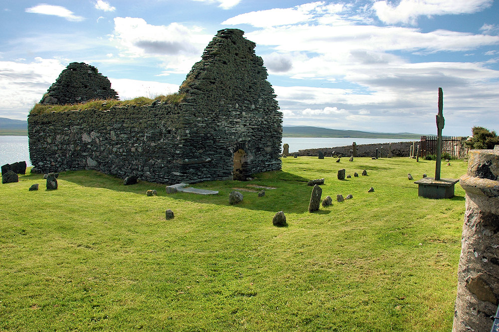 Picture of the ruin of a chapel and a weathered Celtic cross