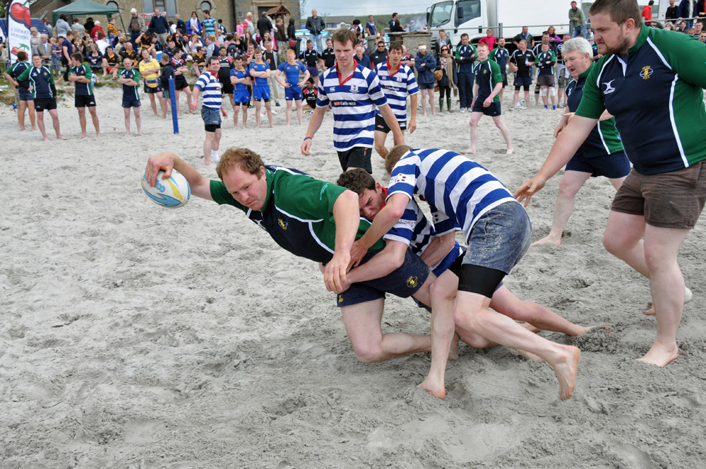 Picture of action during a men's beach rugby game