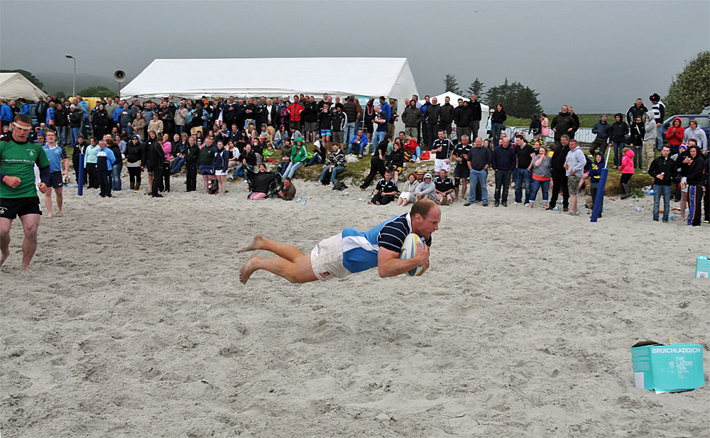 Picture of a flying try in a beach rugby game
