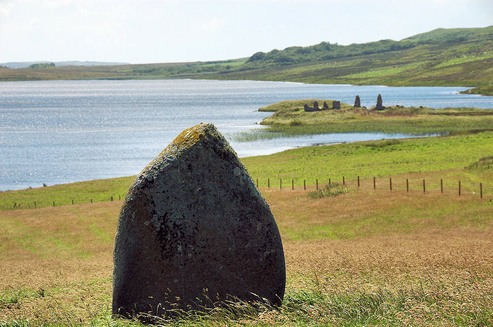 Picture of a small standing stone above a loch with a historic settlement