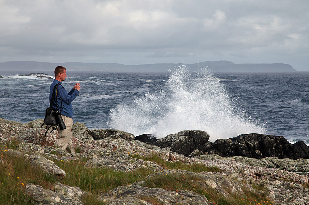 Picture of a man photographing waves breaking over a rocky shore