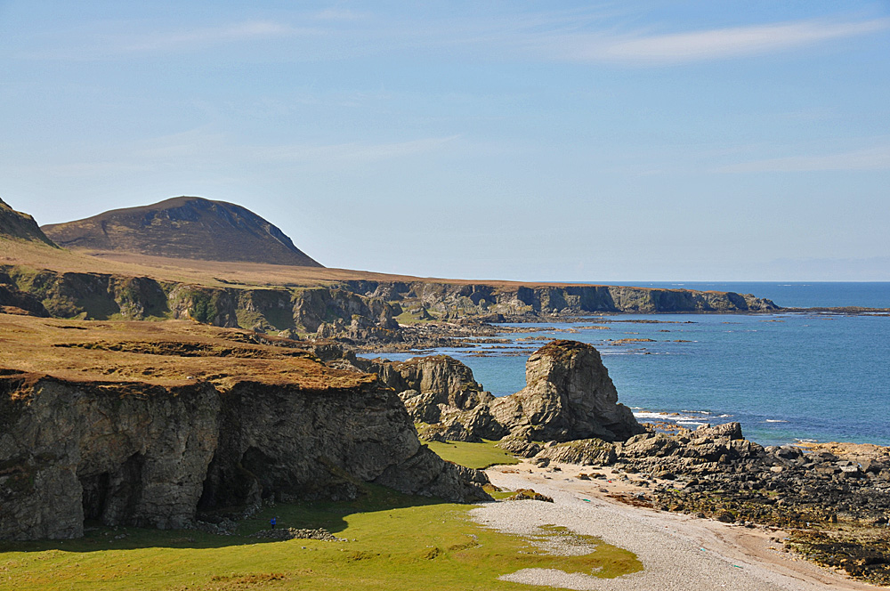Picture of a coastal landscape with cliffs and raised beaches, a big cave in the clifffs