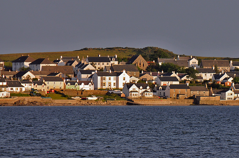Picture of a view of a village across a sea loch, The Bowmore House in the centre