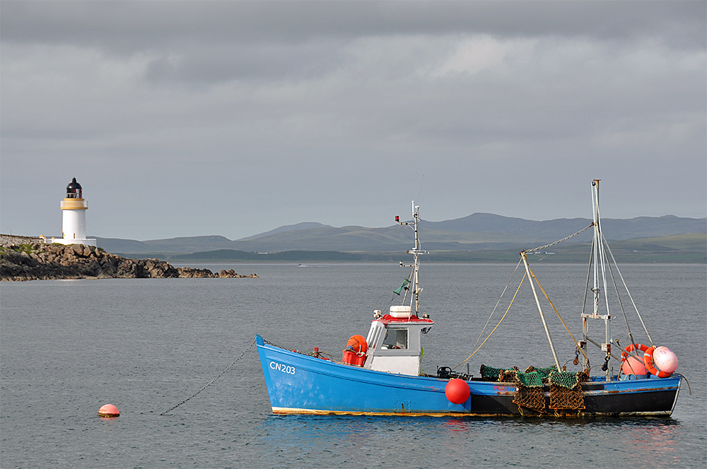 Picture of a fishing boat moored on a sea loch, a lighthouse in the background