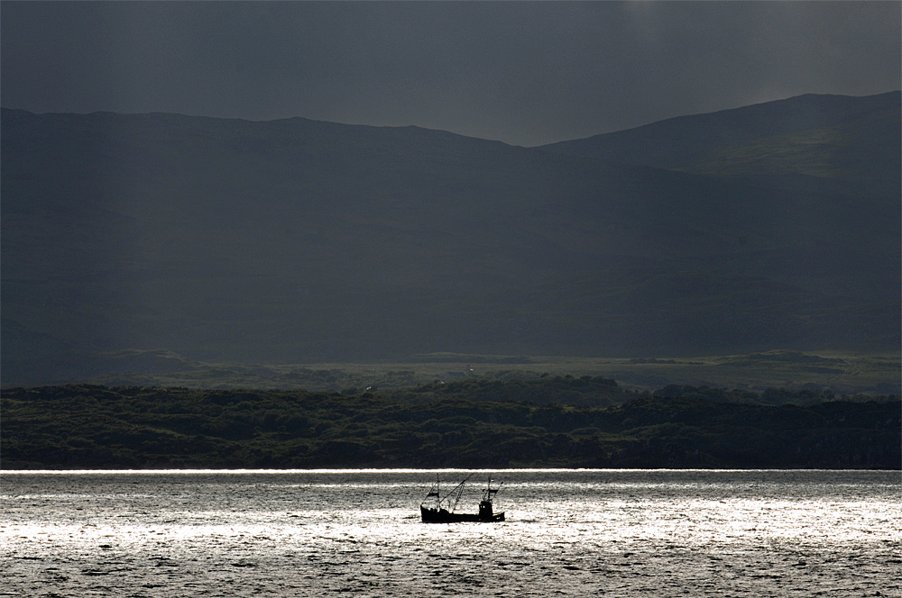 Picture of a fishing boat on water illuminated by a sunbreak, dark clouds above