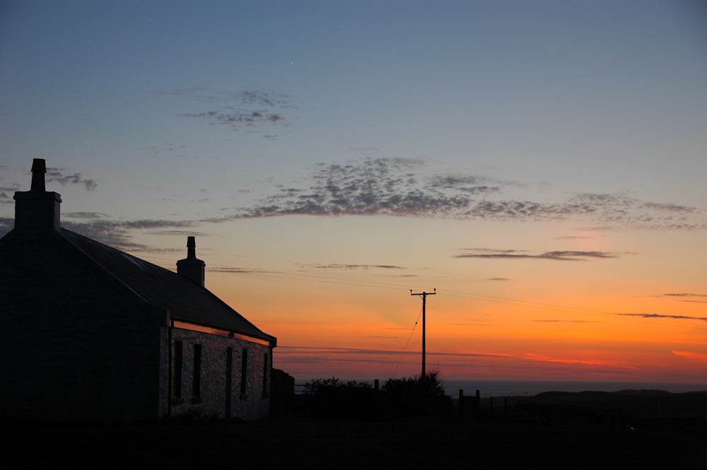 Picture of a cottage in the last evening light, a dramatic red sky in the distance