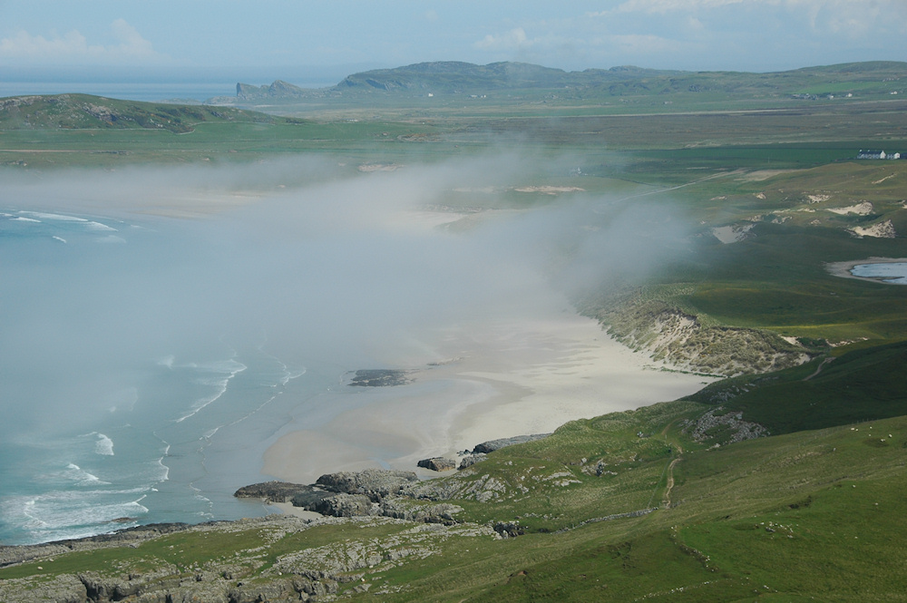 Picture of sea haar rolling into a wide bay with a beach and dunes, seen from above