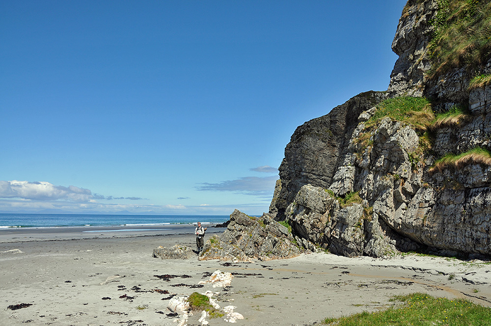 Picture of a woman at the foot of steep cliffs towering over a beach
