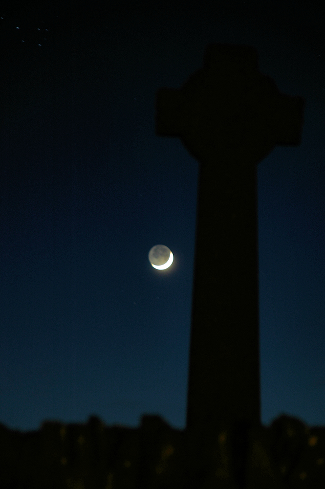 Picture of the Kilchoman Cross (a Celtic cross) with the moon next to it