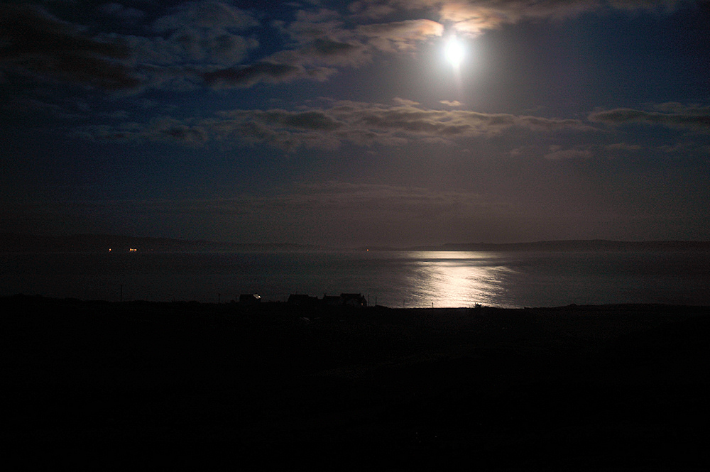 Picture of the moon over a sea loch, seen from a small hill