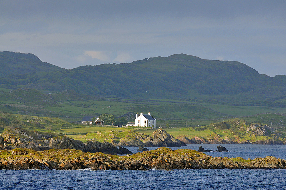 Picture of a beautiful whitewashed house on a coast in the evening sun