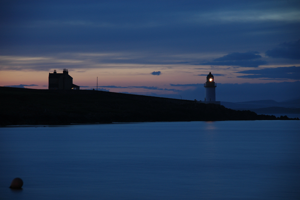 Picture of a lighthouse in the very last light in a June night