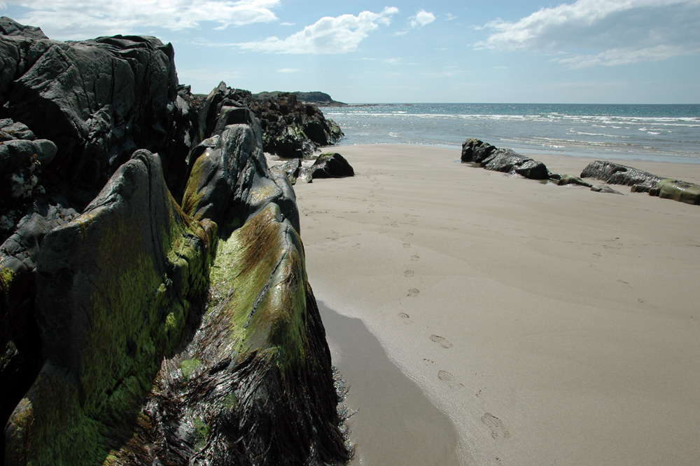 Picture of a beach with footsteps in the sand next to some rocks on the beach