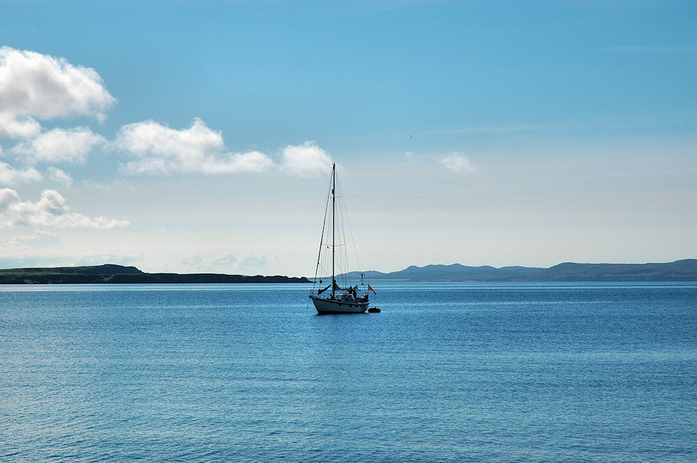 Picture of a sailing yacht anchored on a sea loch on a bright sunny day