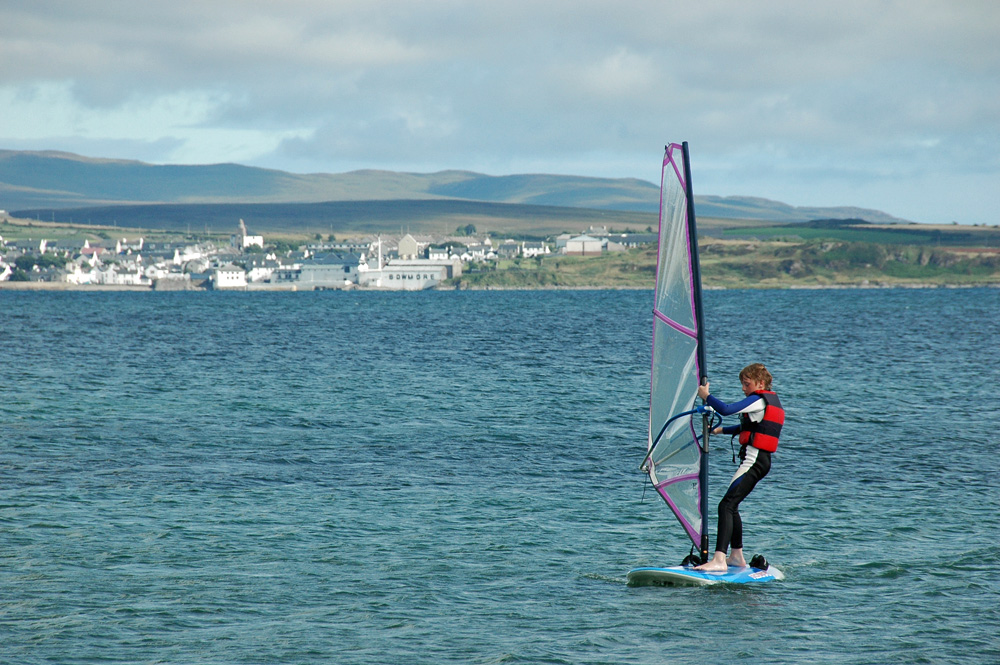 Picture of a boy windsurfing on a sea loch, a village in the background