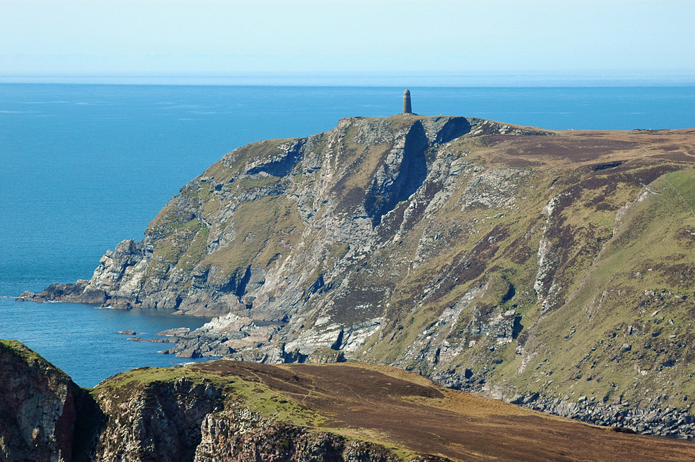 Picture of a monument standing on top of some high cliffs surrounded by the sea