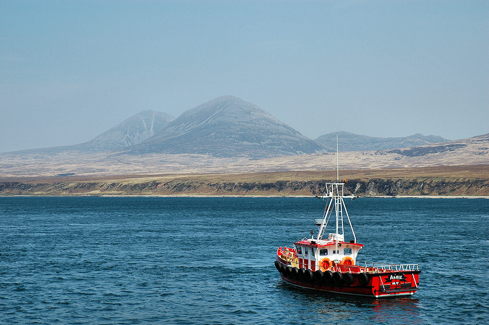 Picture of a red fishing boat anchored in a sound, prominent hills visible on the other shore