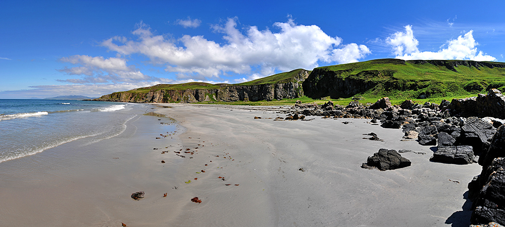 Panoramic picture of a wide beach below some steep cliffs, sunny weather with light clouds