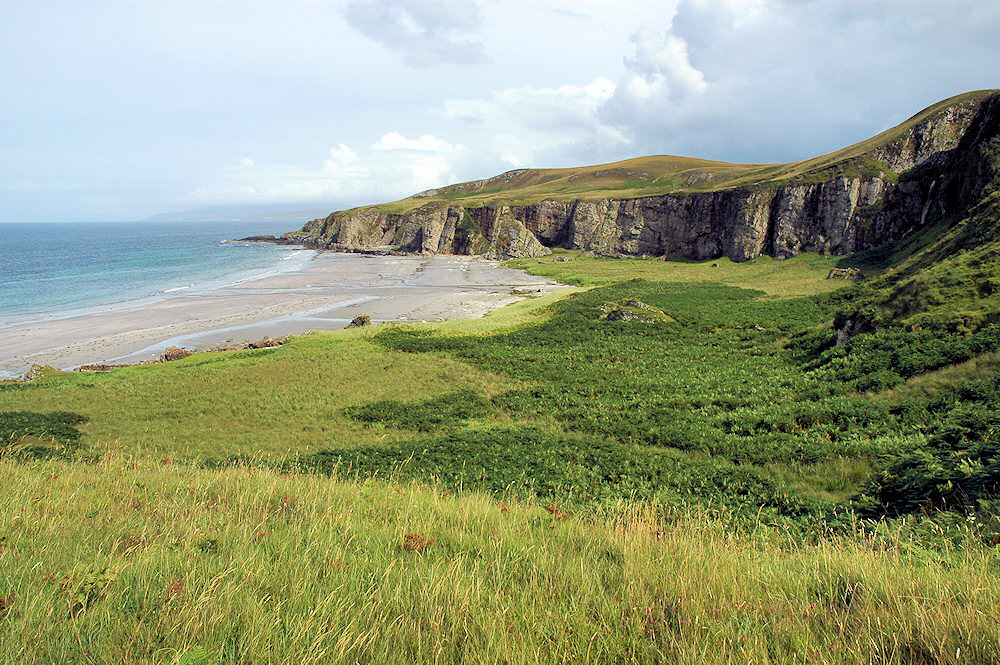 View over a beach surrounded by cliffs