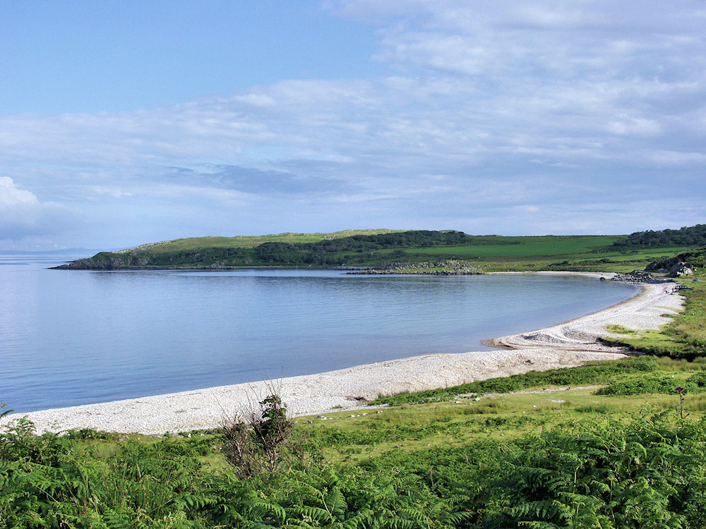 A view over a bay with a pebble beach on a calm evening