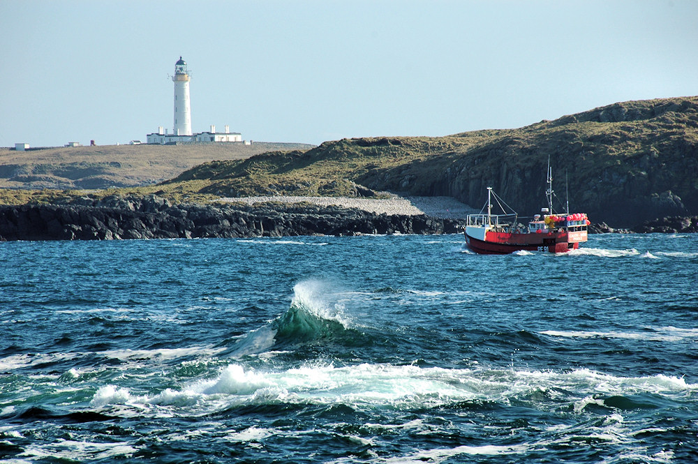 Picture of a small fishing boat passing through a narrow sound, a lighthouse in the background