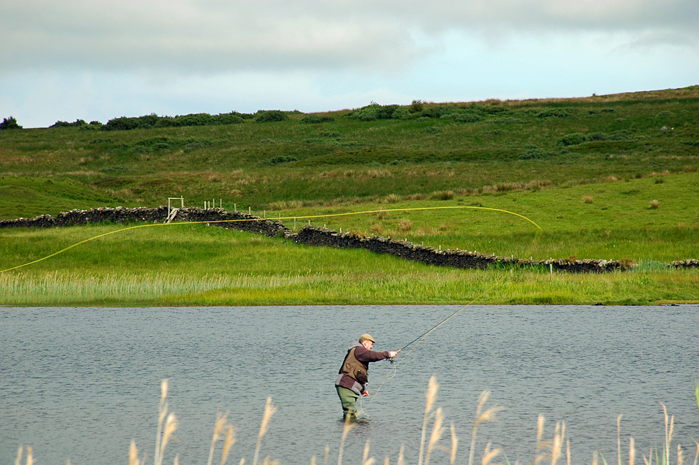 Picture of a man fly fishing in a loch