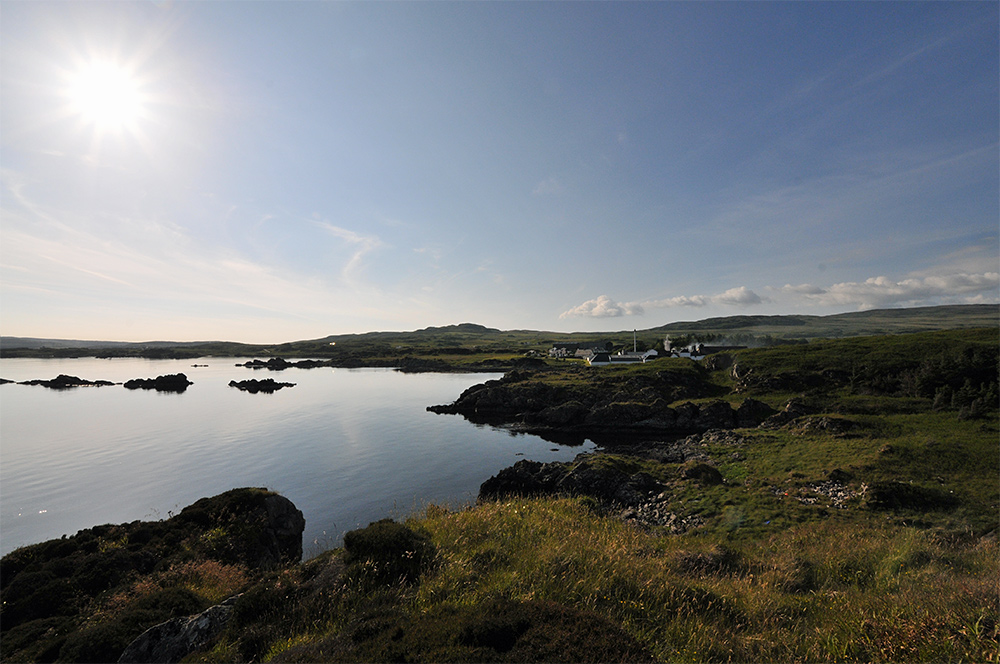 Picture of a rugged coastline in the June evening sun, parts of a distillery visible behind low hills