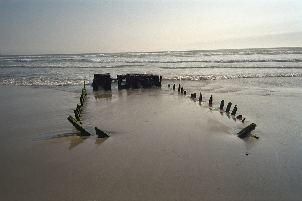 Picture of a wreck sunk in the sand of a beach