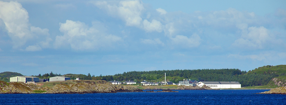 Picture of a coastal distillery, seen across the sea