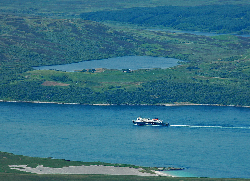 Picture of a view from a hill with a ferry in a sound and loch behind